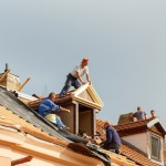 Prague Czech Republic - October 3 2014: Men roofers on the roof make waterproofing and put tile.